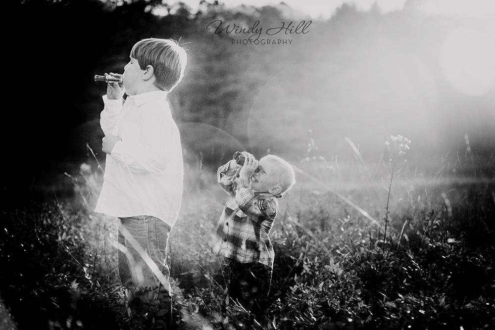 Maine kids photographer brothers duck call binoculars field sunset haze flare.jpg