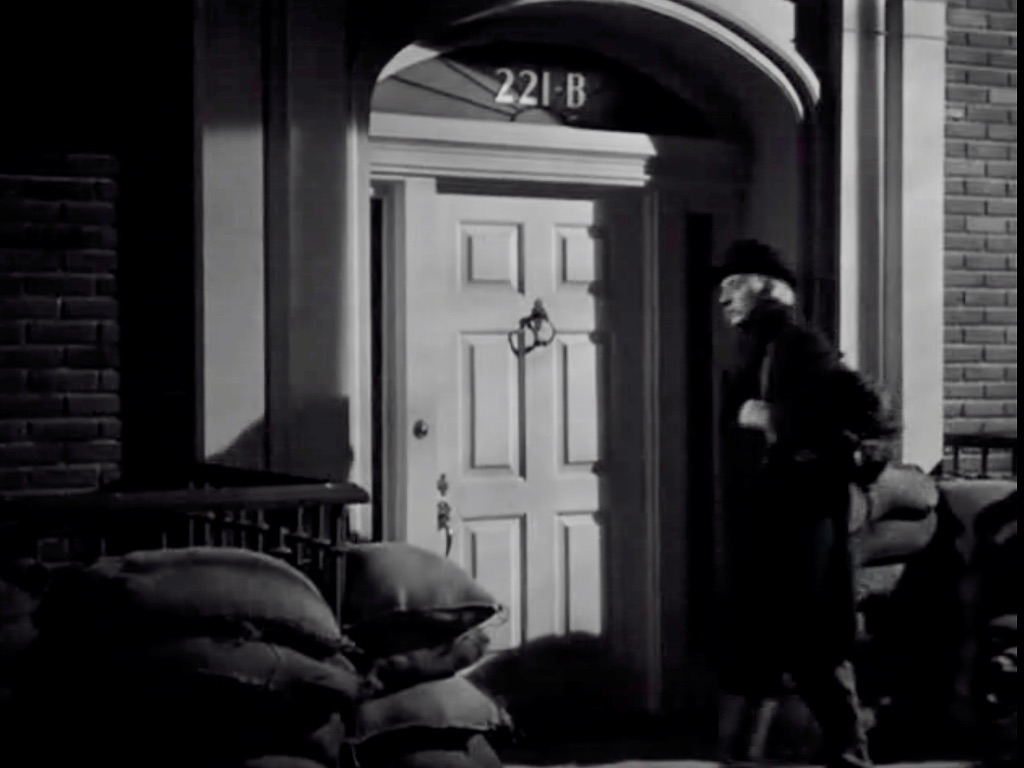 """Here dwell still. . . .""   A still from ""Sherlock Holmes and the Secret Weapon,"" a film set during the Second World War. Here was Basil Rathbone as Holmes, in disguise, ready to walk into 221B Baker Street. Note the sand bags surrounding the door. Despite the destruction all around them, Holmes and Watson still live in Baker Street."