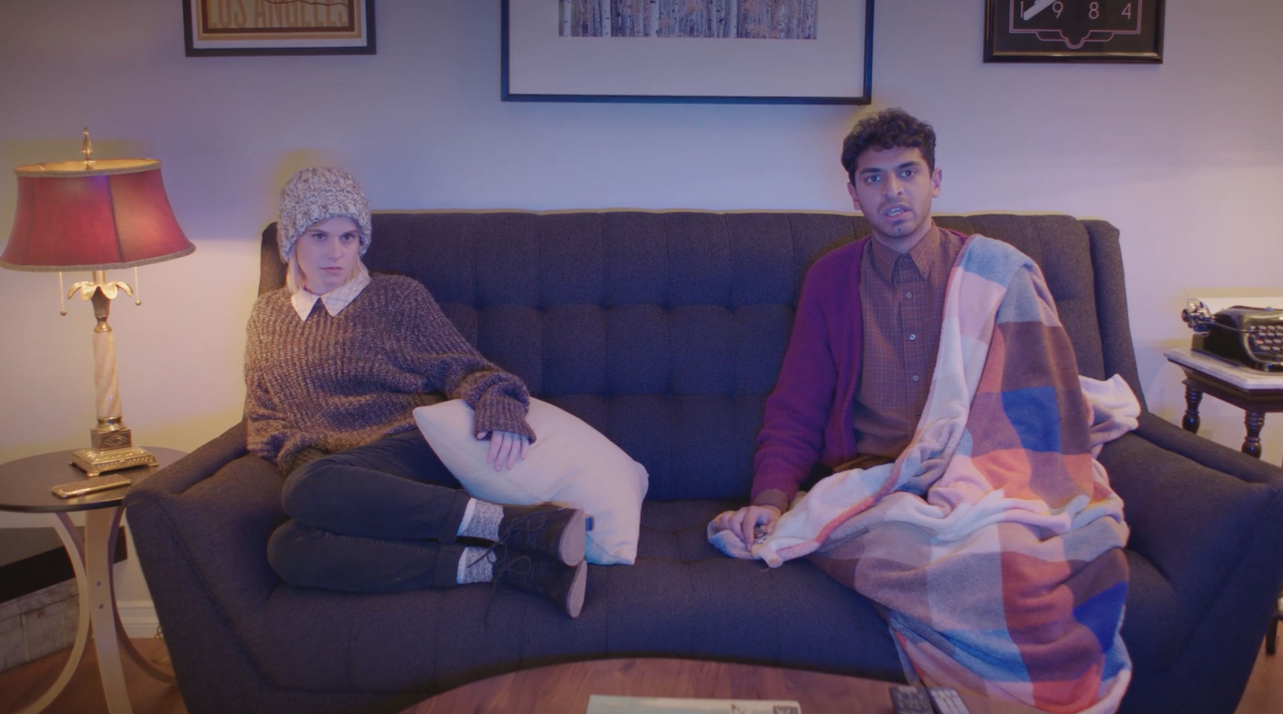 Kate (Carlie Craig) and Bill (Karan Soni) binge their favorite new show Mysterious Artifacts