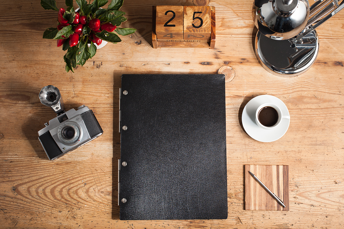 Black leather A4 portrait display portfolio with stainless steel hinges on a desk with a vintage camera and espresso