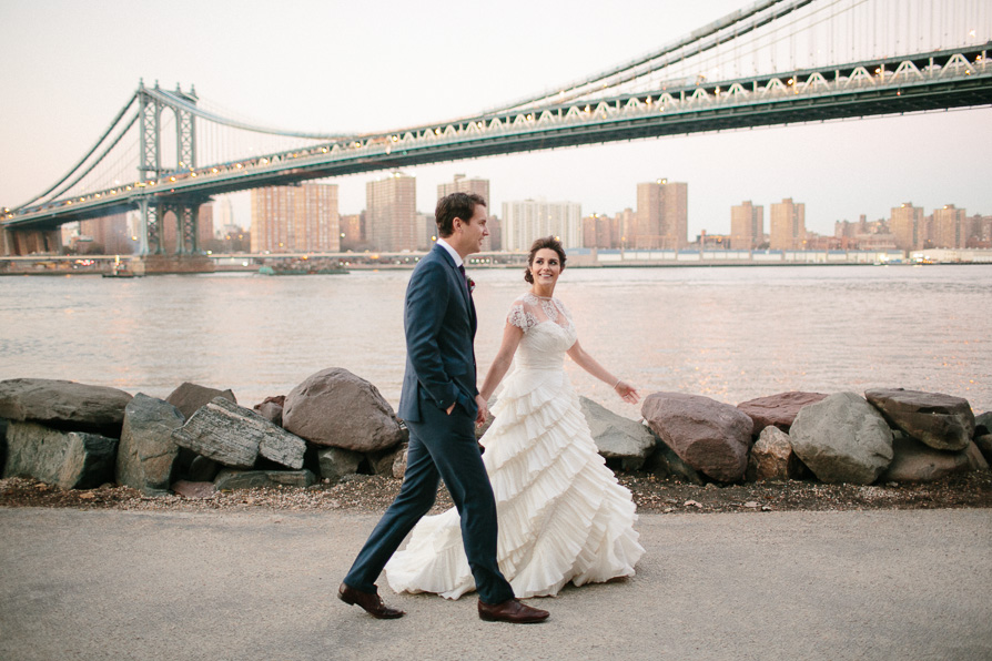 A couple walk in front of the Williamsburg bridge during their day before heading to get hitched at the Music Hall of Williamsburg.