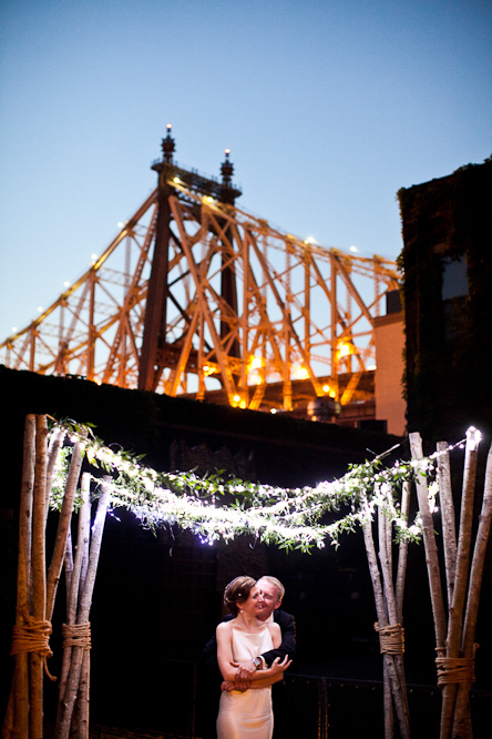 A man and a woman under a Chuppah as the sun sets.