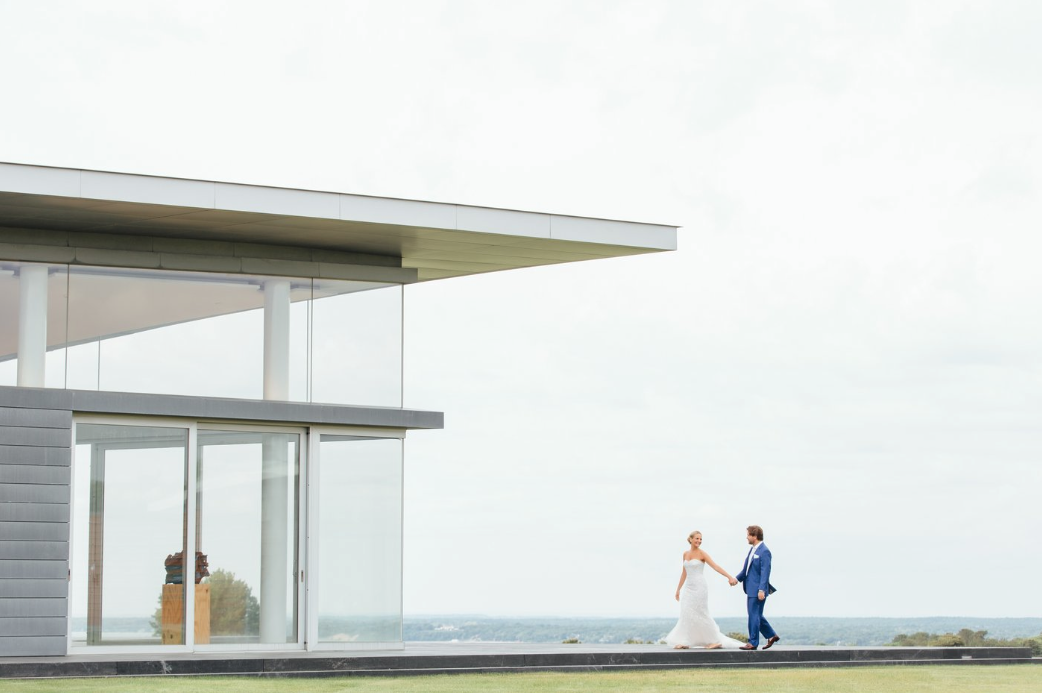 A couple walk through a scene highlighted by the modern architecture of the Bridge Country Club in Long Island