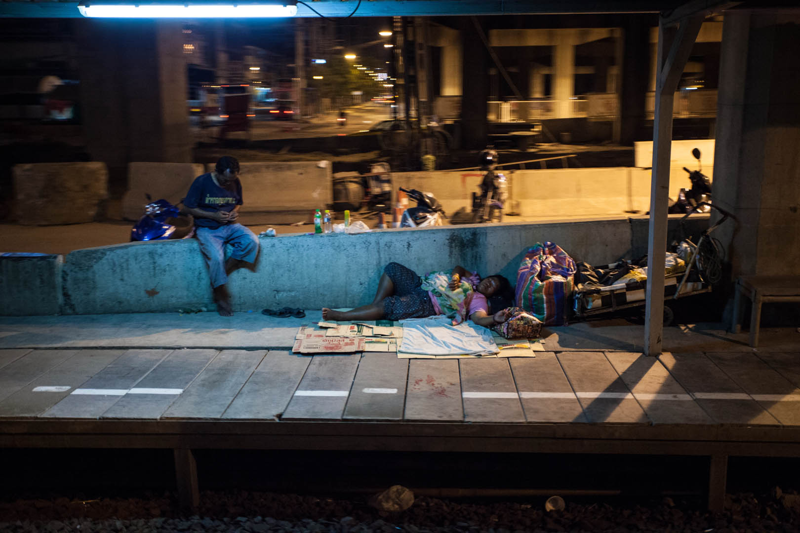 A station in the suburbs of Bangkok. I don't think they are waiting for train...