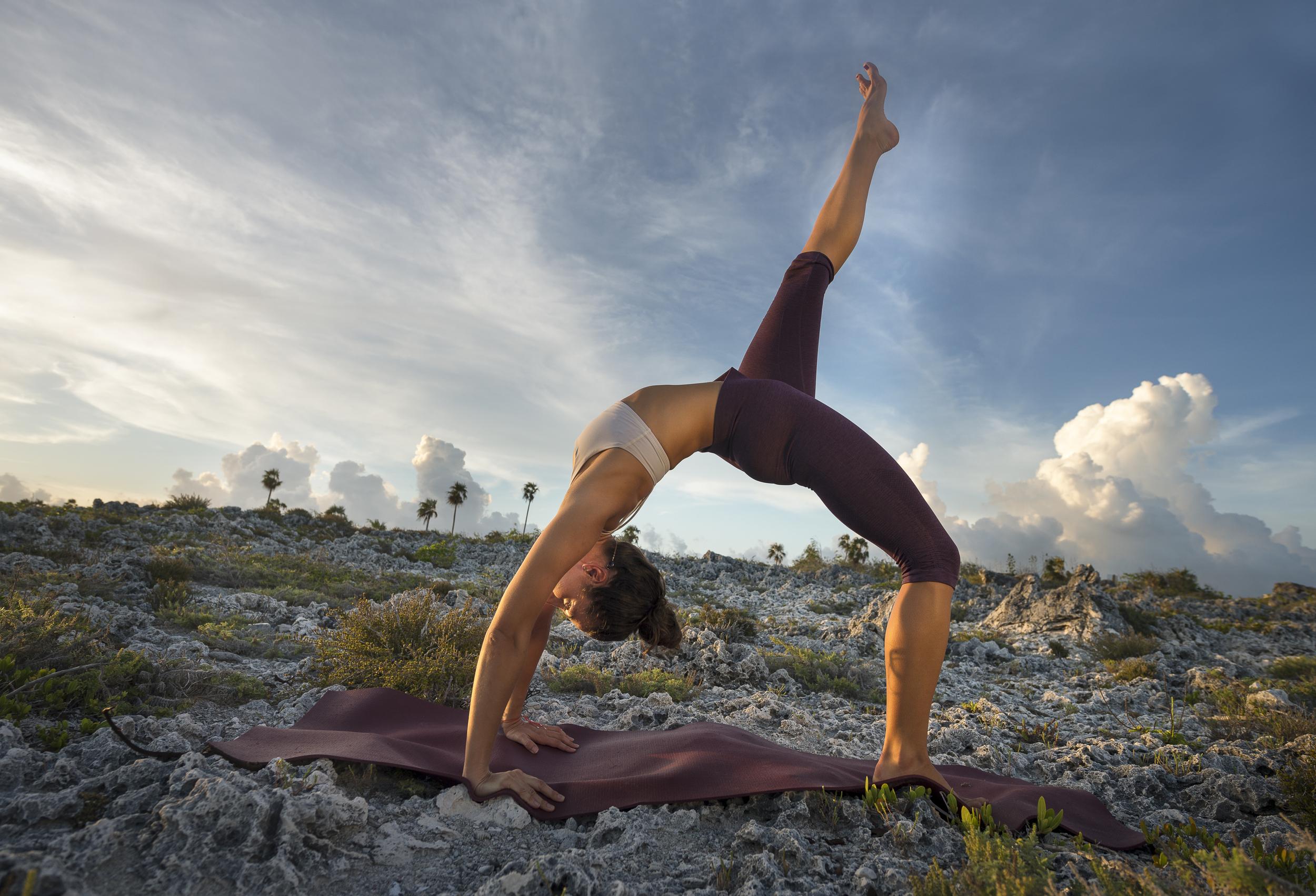 Wheel pose on sunlit cliffs #Yoga