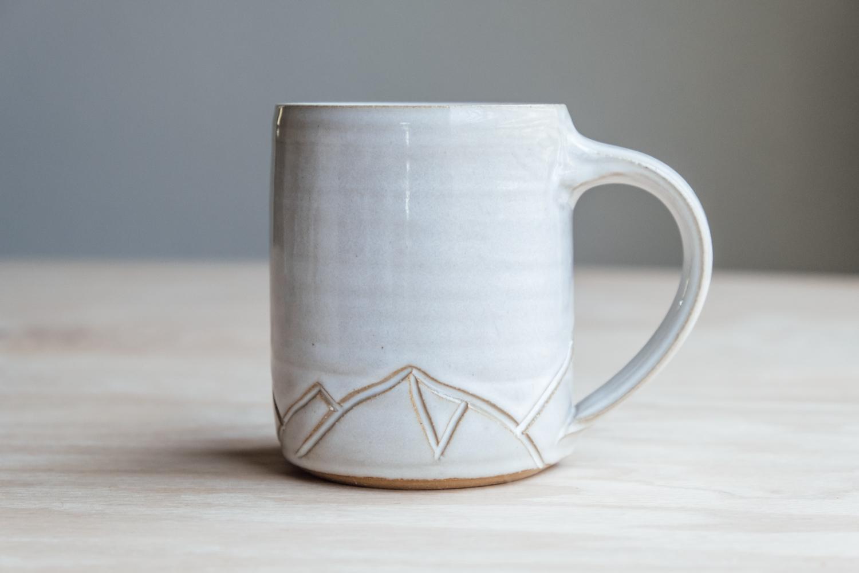 "Mountain Mug - Eggshell   $16.50 Wholesale   $28 MSRP  Approx. 3.75"" tall x 3.25"" wide, 12 oz"
