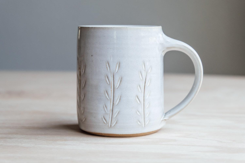 "Meadow Mug - Eggshell   $16.50 Wholesale   $28 MSRP  Approx. 3.75"" tall x 3.25"" wide, 12 oz"