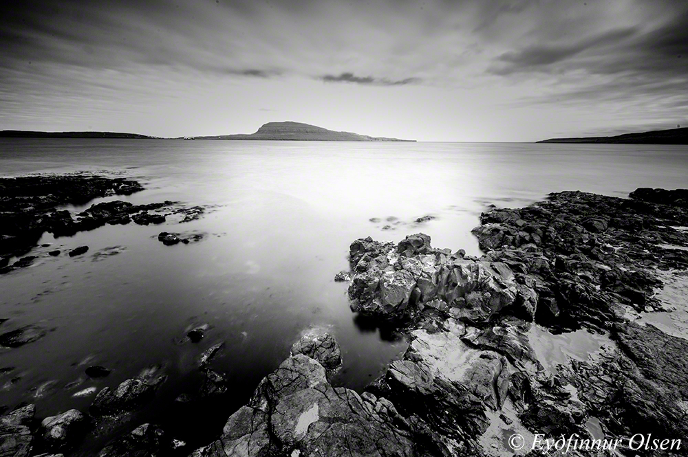 View from a rocky shore in Torshavn with the island Nolsoy in the distance - long exposure photo