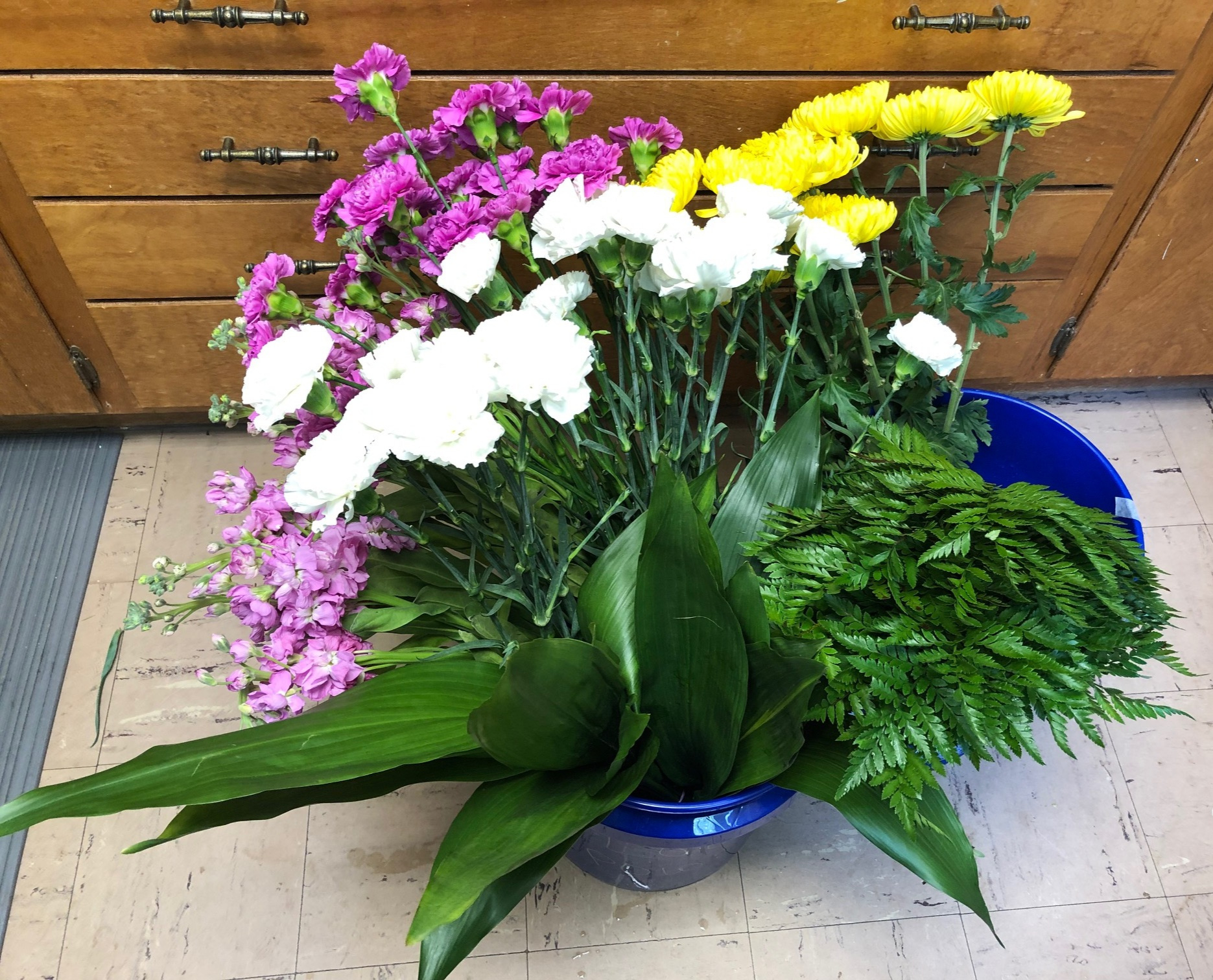 Yellow football mums, white and purple carnations, purple stock, aspidistra, leather leaf fern.