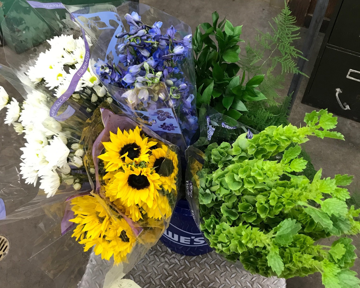 Small sunflowers, purple delphiniums, white pom pom daisies, green bells of Ireland, plumosa fern and Israeli ruscus.