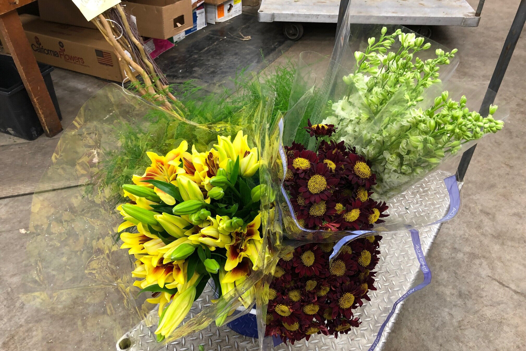 Yellow/burgundy asiatic lilies, burgundy button daisies, white larkspur and tree fern