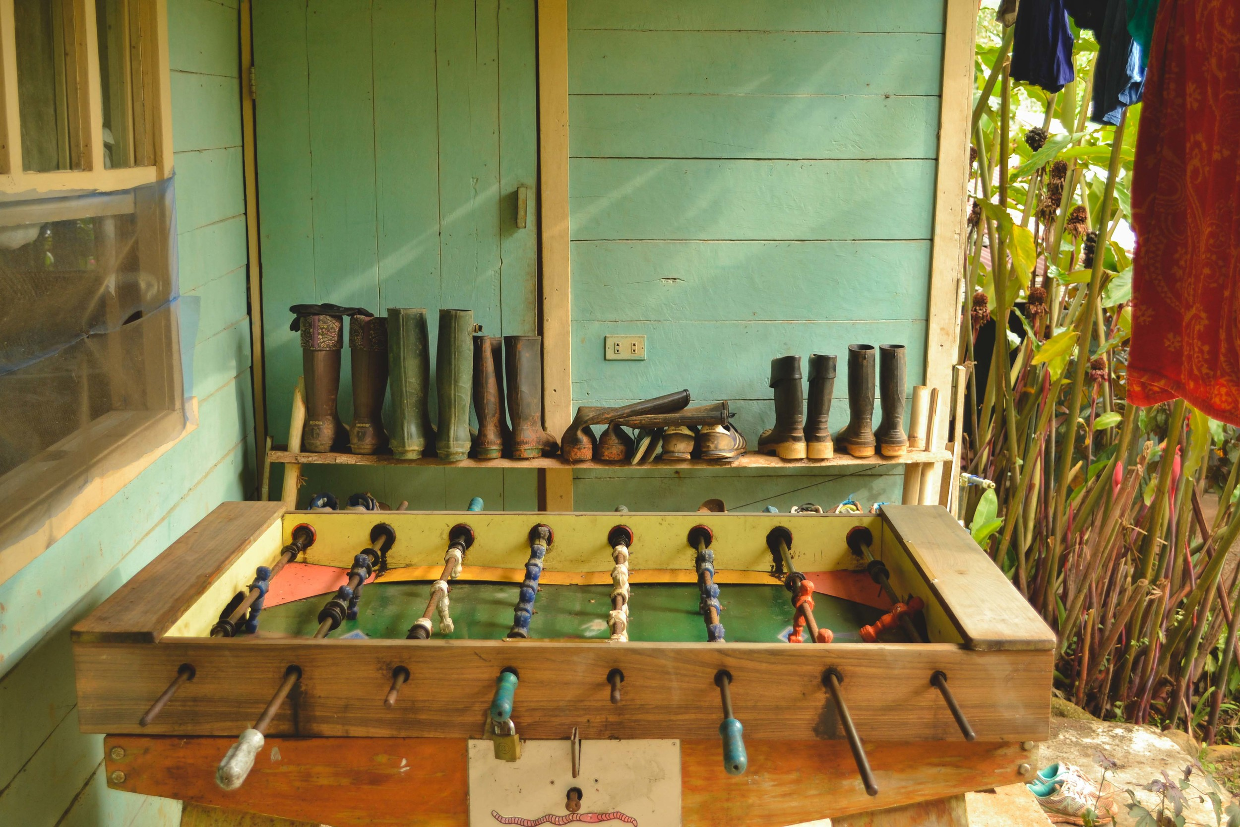 Volunteers' boots arranged near the volunteers' dorm and the foosball table