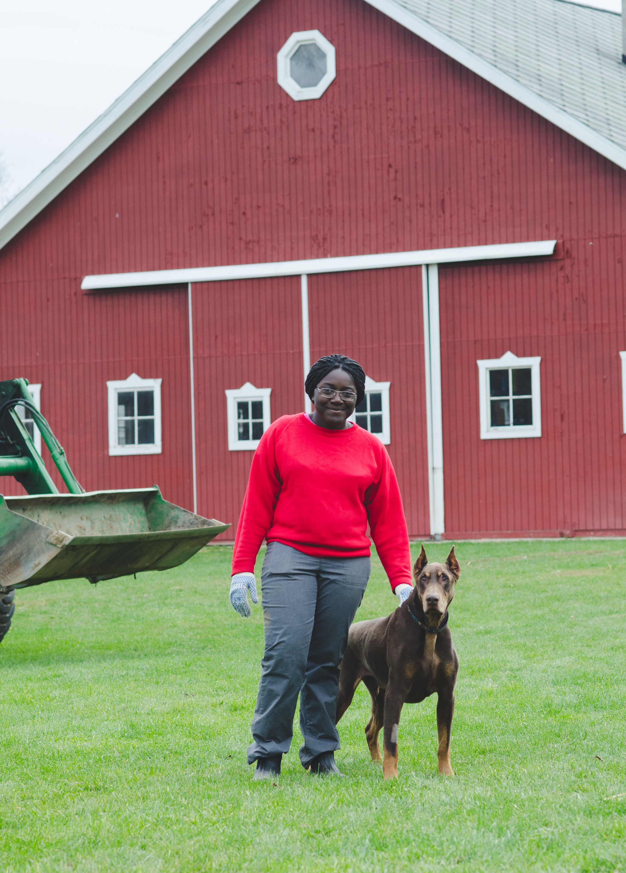 This photo could not get any more Midwest: tractor, red barn, farm dog, work gloves, and muck boots