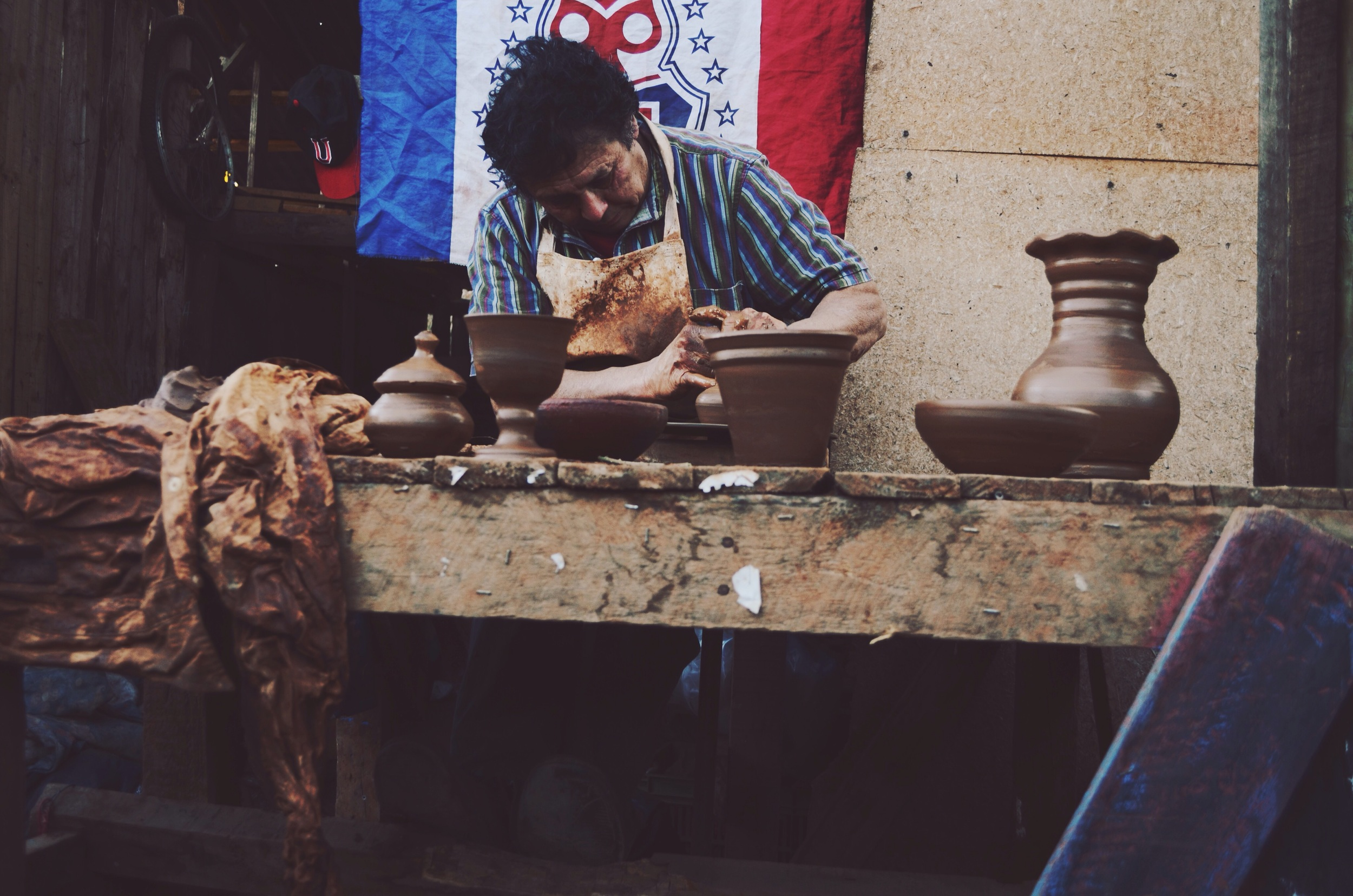he learned from his father (who learned from his father) how to use the potter's wheel, and he can make up to 200 soup-size bowls in one day.  all of the pottery sitting in front of him he made in the span of about 20 minutes. // 9 may 2015