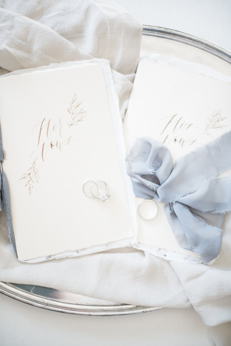 Beautiful calligraphy vow books by  Jolie & Co  with silk ribbon and wedding rings by The Styled Soiree, photo by  Maribeth Photography