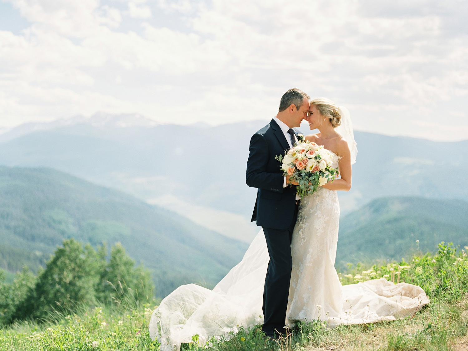 Bride and Groom wedding portraits taken on a mountain top in Vail, Colorado for a Summer wedding