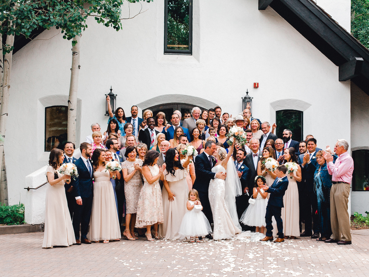 Group photo with all guests on the steps of Vail Interfaith Chapel after wedding ceremony