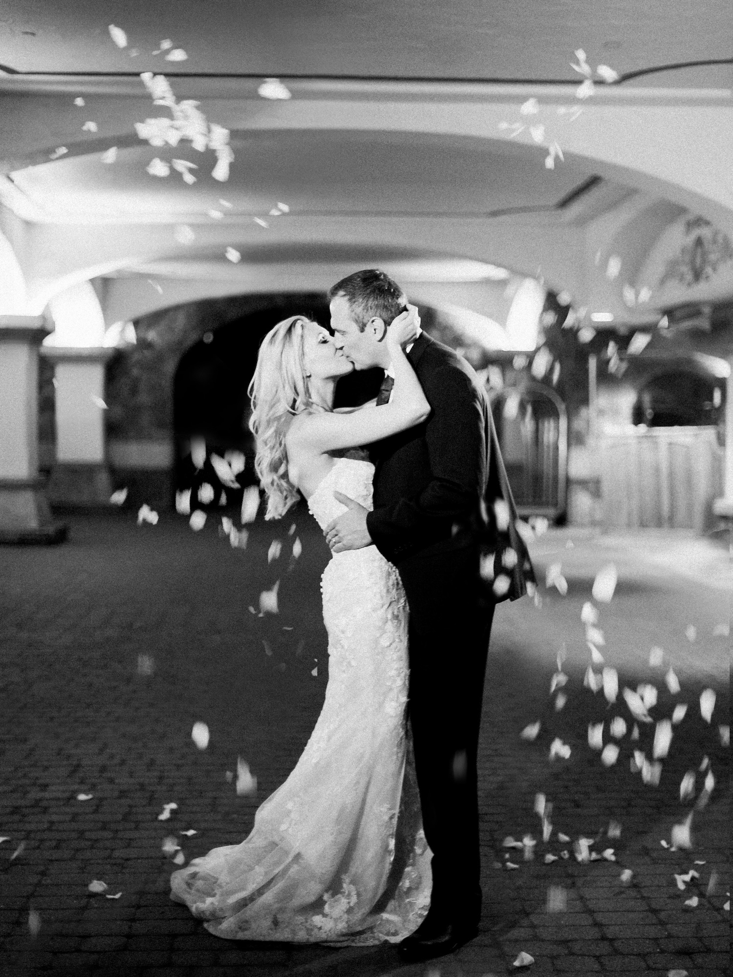 Black and white grand exit photo with petal toss outside
