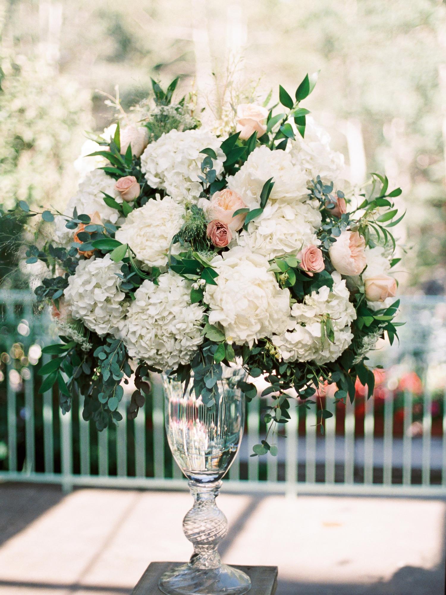 Large floral arrangement in crystal urn for a summer wedding reception