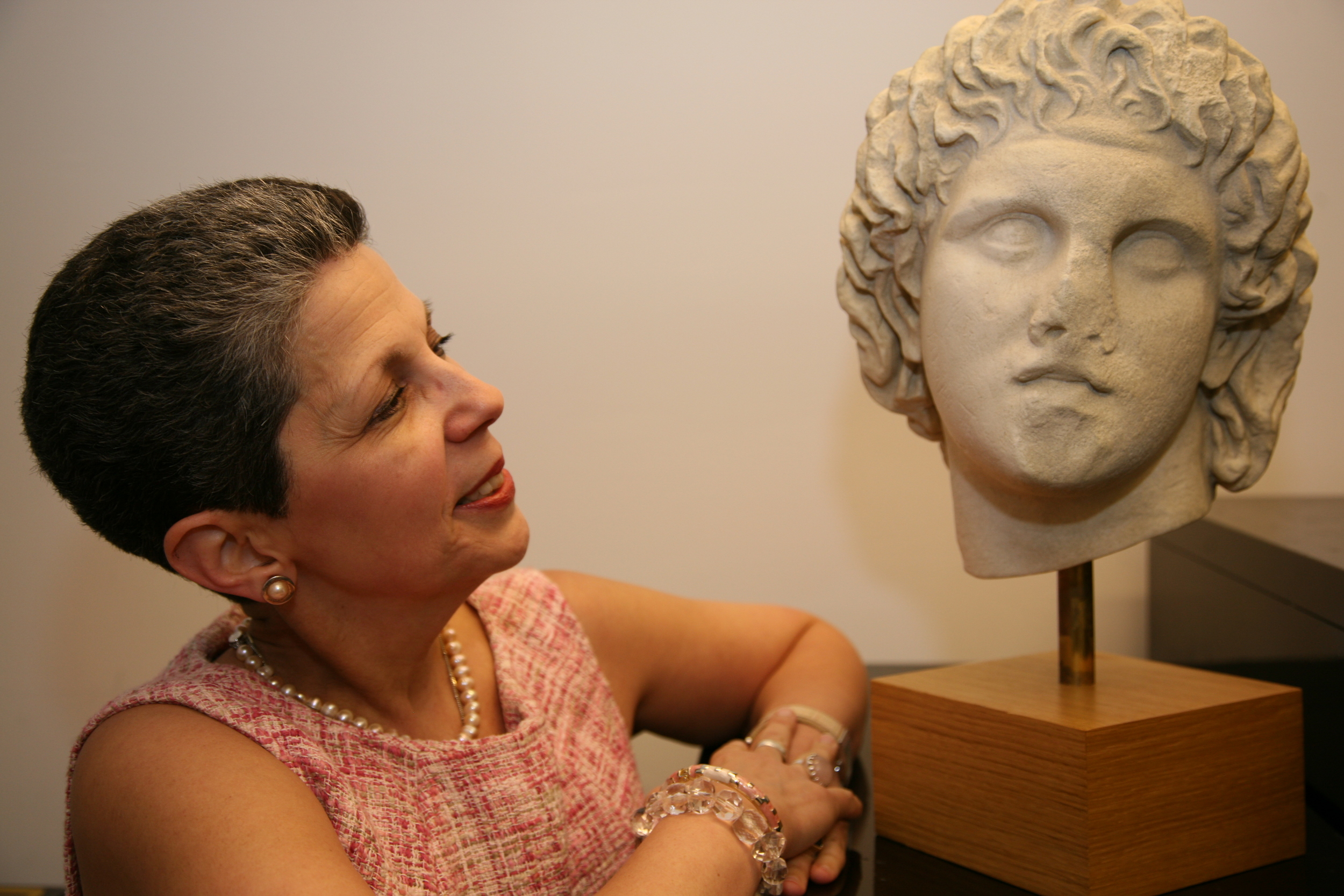 Georgette Gouveia with a copy of a bust of Alexander the Great from the Archaeological Museum of Pella in Greece.  Photograph by Bob Rozycki. Courtesy WAG magazine.