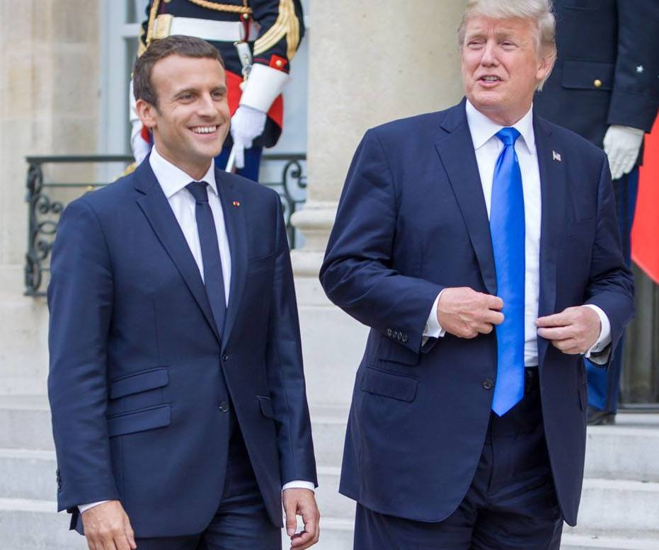 """French President Emmanuel Macron, seen here in Paris with President Donald J. Trump on Bastille Day last year, is left to bridge Iran and Trump now that his """"friend"""" has walked away from the Iran nuclear deal. Courtesy U.S. Embassy/France."""