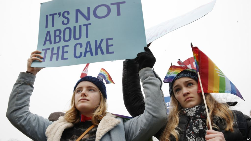 Image via  VOA News . Lydia Macy, 17, left, and Mira Gottlieb, 16, both of Berkeley, Calif., rally outside of the Supreme Court, which is hearing the Masterpiece Cakeshop v. Colorado Civil Rights Commission, Dec. 5, 2017, in Washington.