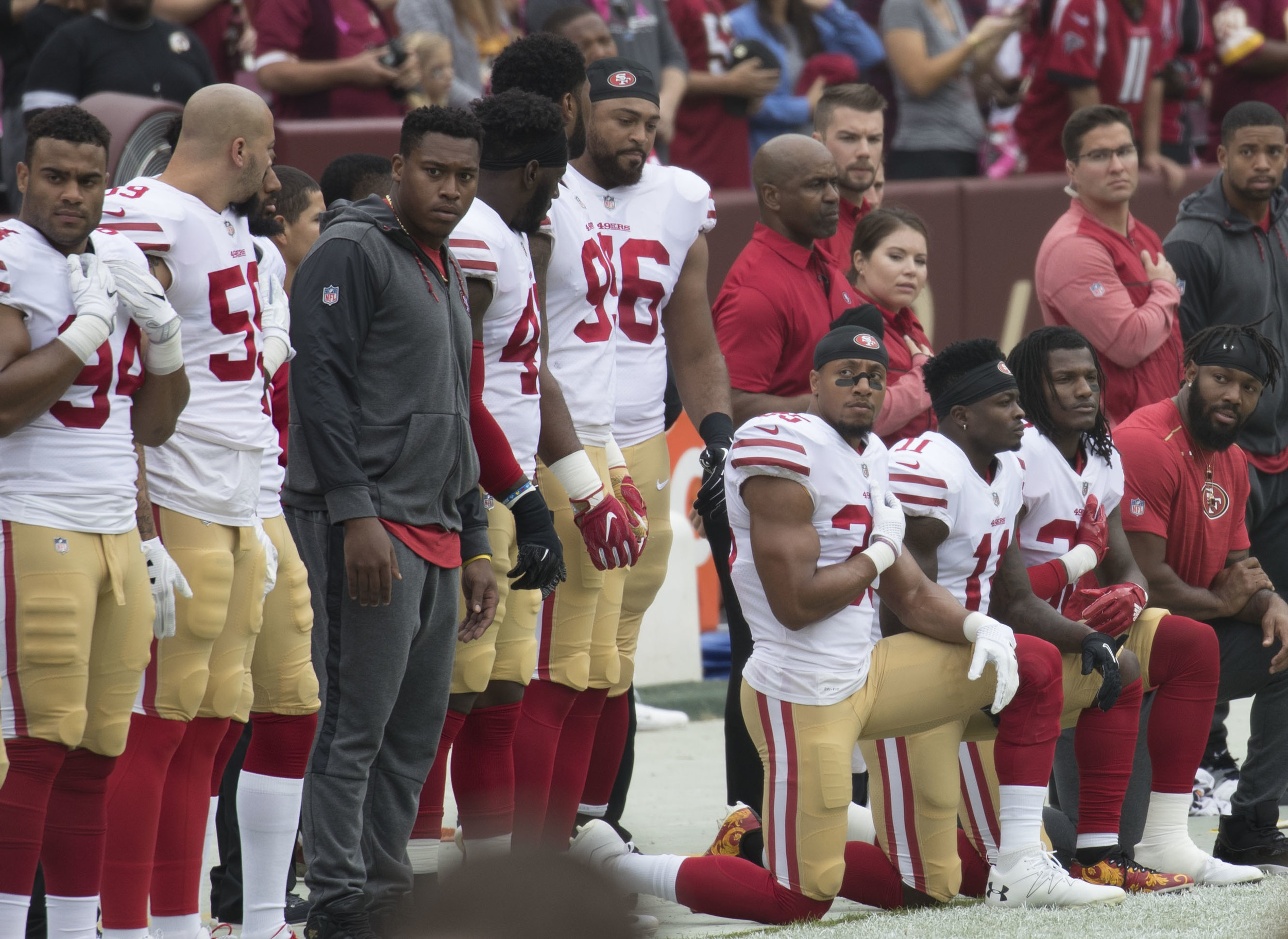 """Some members of the San Francisco 49ers kneeling during """"The Star-Spangled Banner""""before a game against the Washington Redskins at FedEx Field in Landover, Maryland on Oct. 15, 2017. Photograph by Keith Allison."""