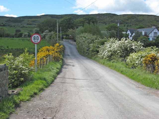 The border on Killeen School Road between Northern Ireland and the Republic of Ireland is marked only by a sign in kilometers. What will happen with this open border is one of the sticking points of Theresa May's Brexit deal. Photograph by Oliver Dixon.