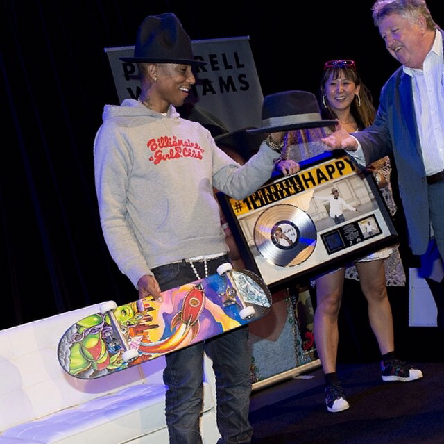 Happy customer Pharrell Williams getting presented the Skateboard by Sony CEO Dennis Handlin.