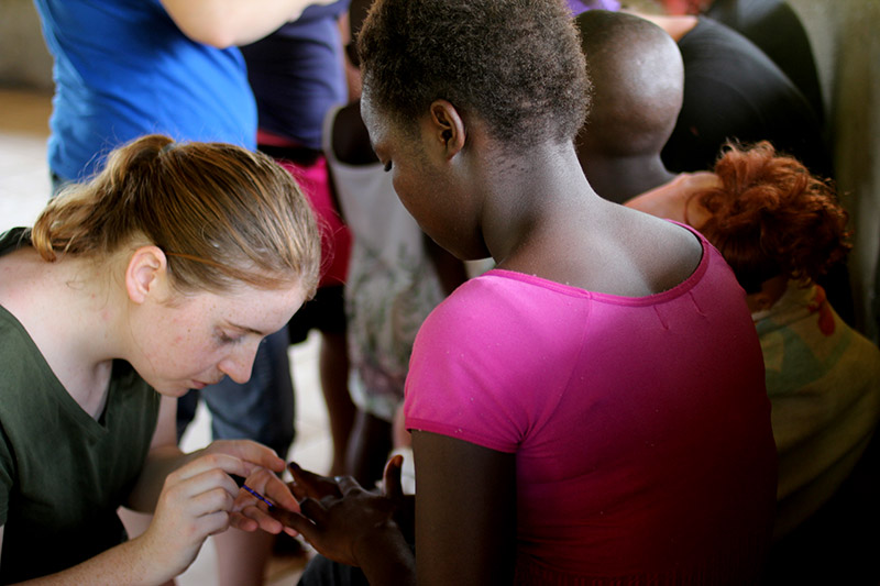 After the children got home from school, everyone gathered in the prayer hut. Some of the ladies on our team painted the girls' nails. Anita carefully painted this girl's nails purple with little flowers. She also cleaned windows, the guest house, and helped Elizabeth with the linens.