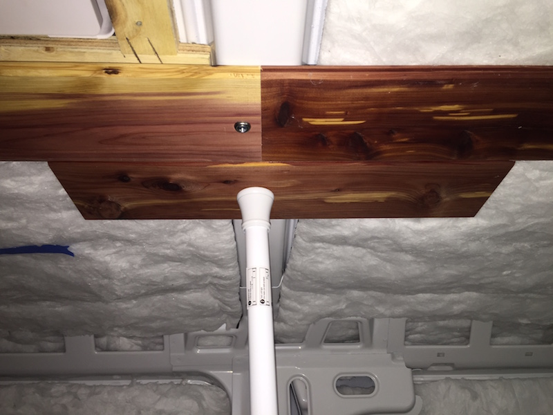 A shower curtain rod secures a soon to be installed plank (R) against an already installed plank (L, with screw). The scrap of plank keeps the newly placed planks aligned during installation.