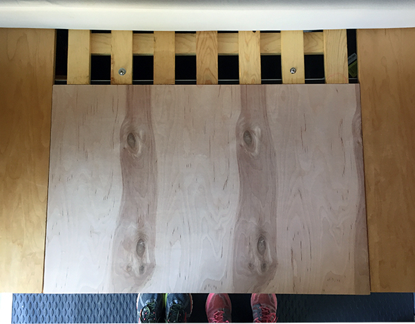Unstained table top inserted in place before install. Slats that form central part of bed frame at top; our feet on van floor at bottom.