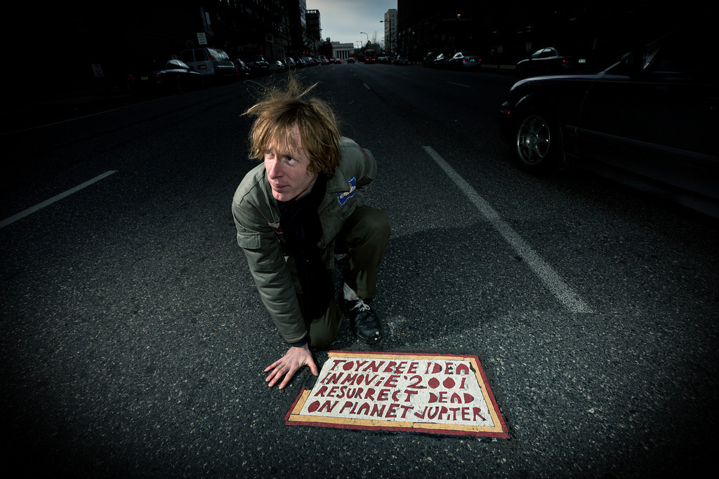 Justin Duerr  next to a  Toynbee Tile  -- from the 2011 documentary,   Resurrect Dead: The Mystery of the Toynbee Tiles .  Photo: © Steve Weinik Photography