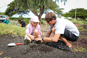 """Tom Loomis, with the Hawaii Wildlife Management Organization, helps Alena Newberg, 7, as they plant native plants at the Waikoloa Dryland Wildfire Safety Park."" Credit - West Hawaii Today"