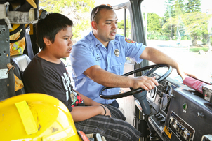 """Firefighter Chuck Segawa gives 12-year-old Micah Canionero a tour of a fire truck during the day of fire preparedness at Waikoloa Dryland Wildfire Safety Park on Saturday."" Credit - West Hawaii Today"