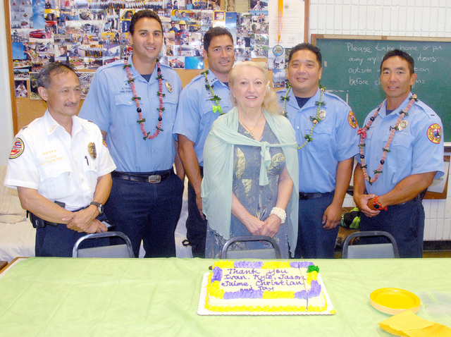 """Above: """"Dee Faessler center brought cake, ice creamand leis to the Kailua Fire station on Tuesday as a thank you to paramedics including from right Ivan Higashi, Jamie Okuda, Tay Soares, Kyle Teves and Battalion Chief Reuben Chun for taking care of her on multiple trips to the Kona Hospital Emergency Room."""" Credit - Laura Shimabuku/Special to West Hawaii Today"""