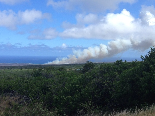 "Above: ""Firefighters are getting the upper hand on a brush fire that consumed more than 1,000 acres after igniting Sunday afternoon near Kaalualu Bay in Ka'u. This photo shows smoke rising from the blaze on Sunday afternoon."" Credit: Pierce Schwalb/West Hawaii Today"