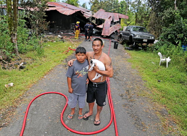 """Above: """"Van Uemura Jr. hugs his son, Cameron Uemura, while holding their puppy in front of their Hilo home, which was destroyed in a fire Friday.""""Credit: Hollyn Johnson / Stephens Media Hawaii"""
