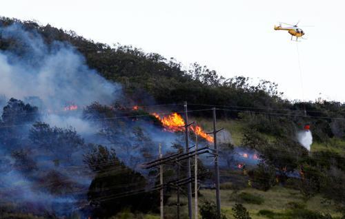 "Above: ""Honolulu firefighters battled a brush fire Friday above Umena Street in Makakilo.""Credit - Krystle Marcellus/Star Advertiser"