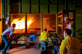 """Above: """"Scientists at the Fire Sciences Laboratory in Missoula observe the behavior of fire in a wind tunnel."""""""