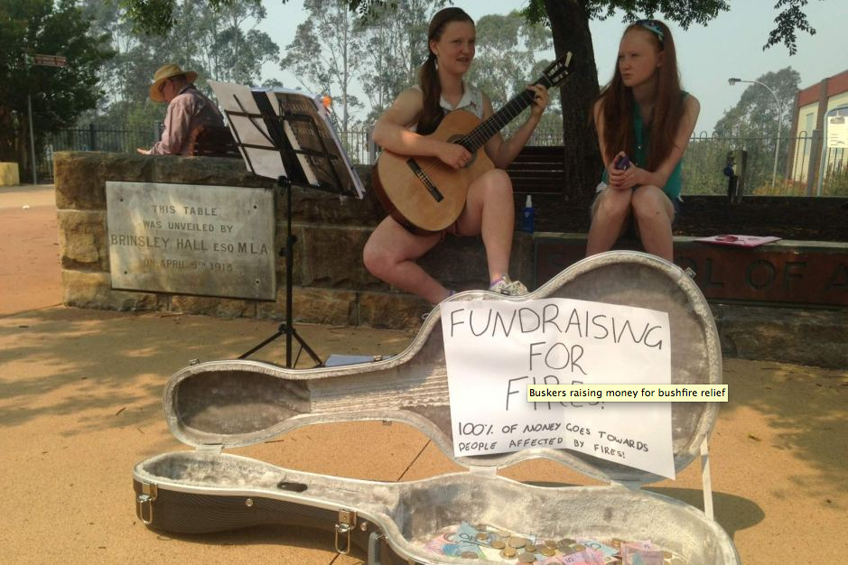 "Above: ""Alecia Newton and Mairead Sheehy busking on Springwood's shopping strip, Macquarie Street on October 20, 2013, to raise money for those who have lost homes in the fire."""