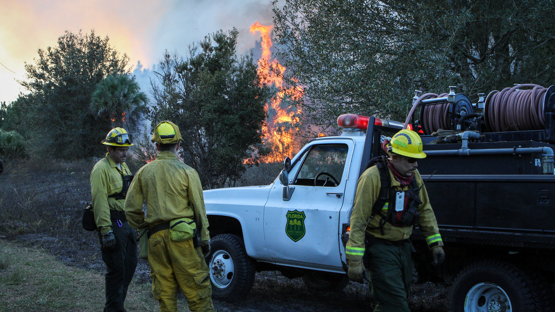 """Above: """"Crews work a controlled burn in Geneva, Fla., in December. The state's forest service has rolled out a system to track equipment during fires, and hopes it can eventually be used to pinpoint firefighters, too."""" - NPR"""