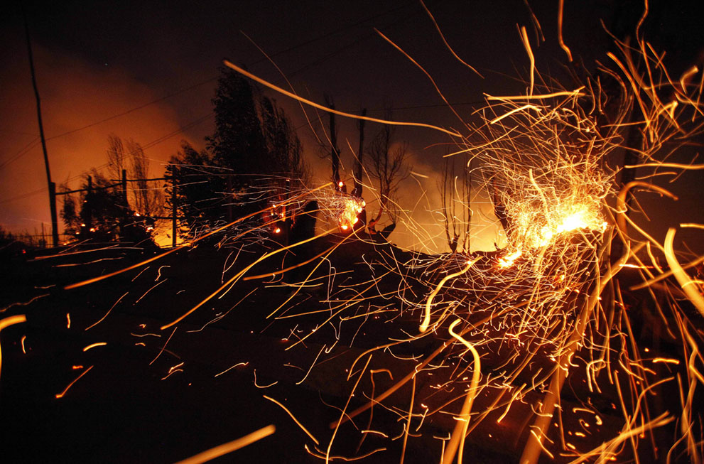 "Above: ""Embers are carried by high winds as a large forest fire reaches urban areas in Valparaiso, Chile, on April 13, 2014. Authorities say the fires destroyed thousands of homes, forced the evacuation of more than 100,000 and claimed the lives of at least 12 people."" AP Photo/Luis Hidalgo."