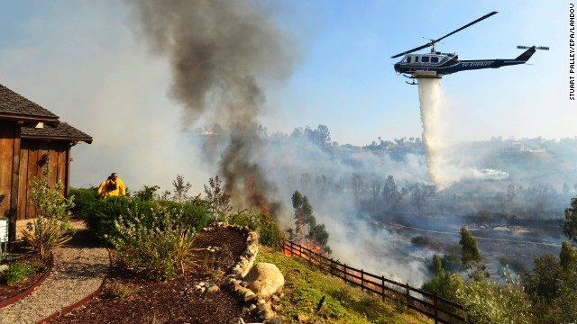 """Above: """"A helicopter drops water near the Rancho Santa Fe neighborhood of San Diego on Tuesday, May 13. A wildfire forced the evacuation of more than 20,000 homes in Southern California, officials said, as a high-pressure system brought unseasonable heat and gusty winds to the parched state."""" Credit:Stuart Palley/EPA/Landov"""