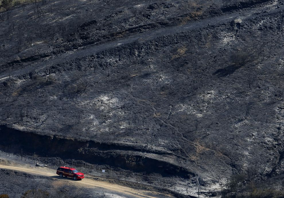 """Above: """"Firefighters drive through a burned-out area in the hills around San Marcos, California, on May 15, 2014."""" Credit:Mike Blake/Reuters"""