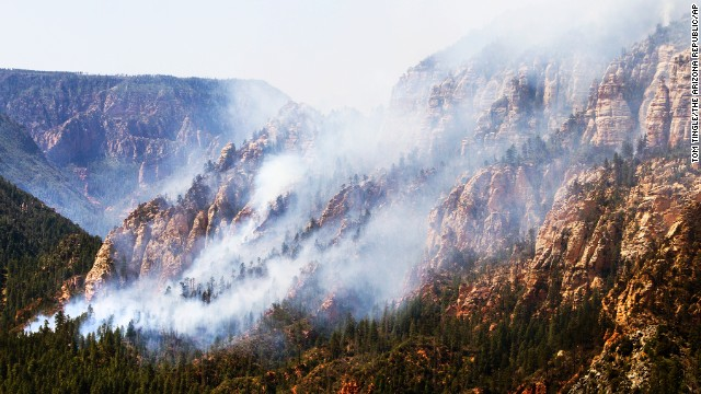 """Above: """"A wildfire burns south of Flagstaff, Arizona, on Wednesday, May 21. The fast-growing fire, dubbed the Slide Fire as it is just north of Slide Rock State Park, threatens several hundred homes and rental cabins in the area."""" Credit: CNN"""
