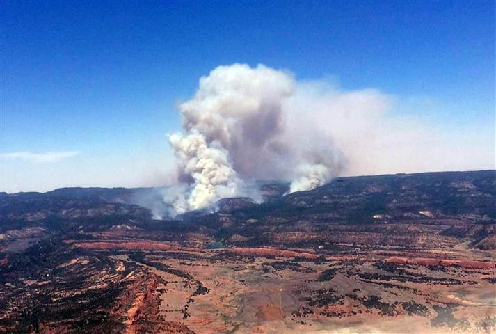 """Above: """"A plume of smoke in the Chuska Mountains near Naschitti, N.M. on June 15. Residents of a Navajo community near the New Mexico-Arizona border prepared for evacuations Monday as strong winds fanned the flames of a wildfire burning in the Chuska Mountains."""" Credit: Associated Press"""