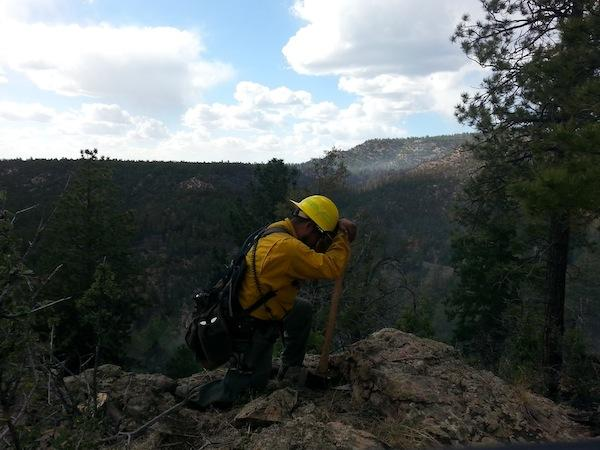 "Above: ""A weary firefighter prays between bouts with the Assayii Lake Fire in the sacred Chuska Mountains on the Navajo Nation."" Credit: Neil Damon"