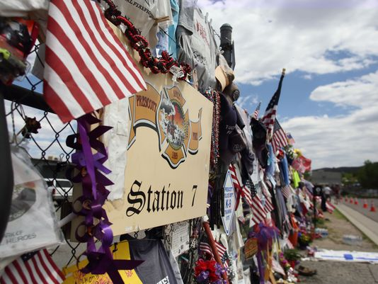 """Above: """"A makeshift memorial to the 19 fallen firefighters wraps around three sides of Fire Station 7 in Prescott in August, weeks after the tragedy."""" Credit: Lynn French / The Arizona Republic"""
