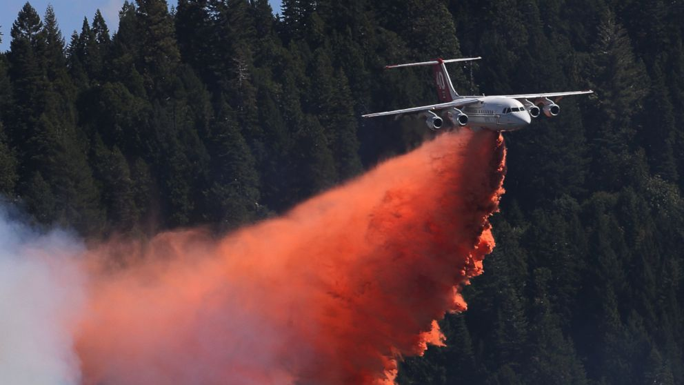 """Above: """"A jet aerial tanker drops its load of fire retardant on a fire near Pollack Pines, Calif., Monday, Sept. 15, 2014. The fire, which started Sunday has consumed more than 3,000 acres and forced the evacuation of dozens of homes."""" Credit - Rich Pedroncelli/AP Photo"""
